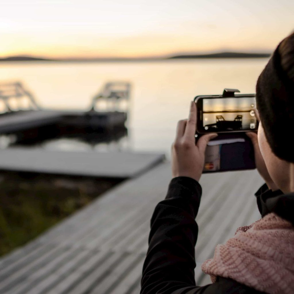 A girl taking a picture of a dock with two chairs while getting to know local villages in lapland.
